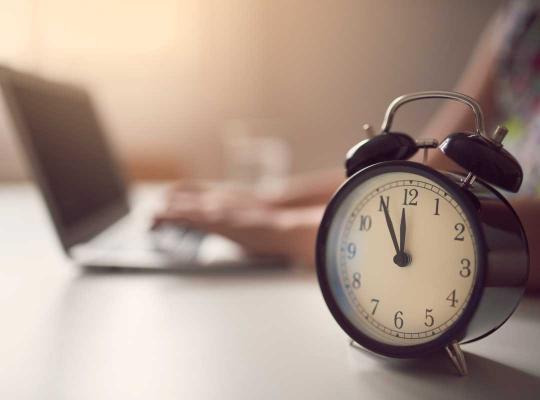 Vrouw aan het werk met klok op voorgrond